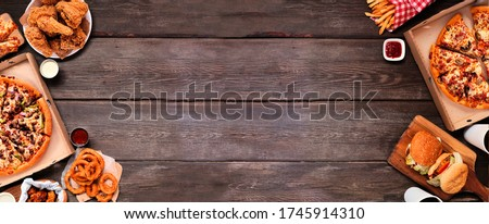 Assortment of take out or delivery  foods. Pizza, hamburgers, fried chicken and sides. Double side border. Top view on a dark wood banner background with copy space. Stockfoto ©