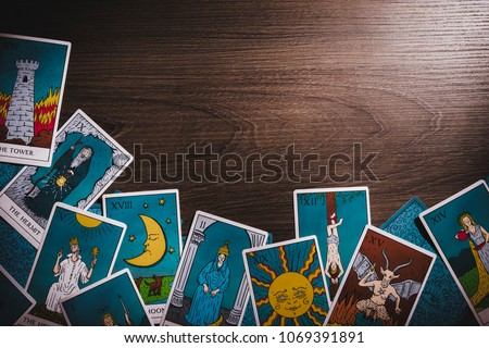Assortment of Tarot inspired cards on a wooden background #1069391891