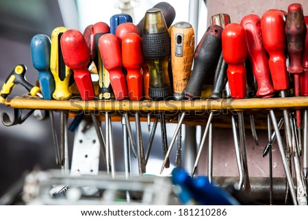 Assortment of tools hanging on the wall. Many screwdrivers in mechanic garage car service