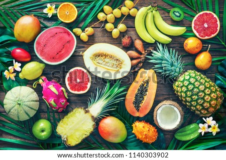 Assortment of tropical fruits with leaves of palm trees and exotic plants on dark wooden background. Top view