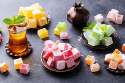 Assortment of Turkish delights on a copper tray with glass of tea. Grey background.