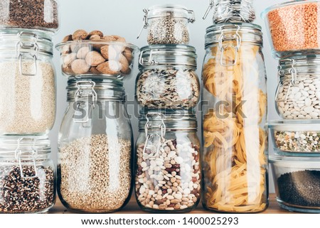 Assortment of uncooked grains, cereals and pasta in glass jars on wooden table. Healthy cooking, clean eating, zero waste concept. Balanced dieting food.