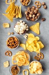 Assortment of Unhealthy Snacks: chips, popcorn, nachos, pretzels, onion rings in bowls, top view, flat lay. Unhealthy eating concept.