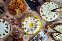Assortment of various cakes fresh from the workshop on wooden table. Assortment of cakes for special celebrations