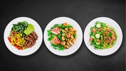 Assortment of various healthy keto paleo meals on white plate. Black stone background. Top view. Isolated. Space for text.