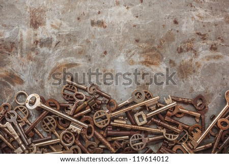 Assortment of vintage keys on a grungy steel background