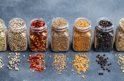 Assortments of spices, white pepper, chili flakes, lemongrass, coriander and cumin seeds in jars on grey stone background.