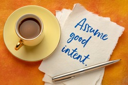 assume good intent inspirational handwriting on a piece of handmade paper with a cup cooffee, positivity concept