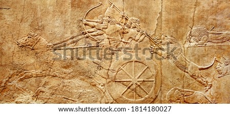 Assyrian wall relief of lion hunt, king Ashurbanipal with warriors on carving from Middle East and Mesopotamia. History of past civilization of Iran and Iraq. Monument of Assyria and Babylon culture.