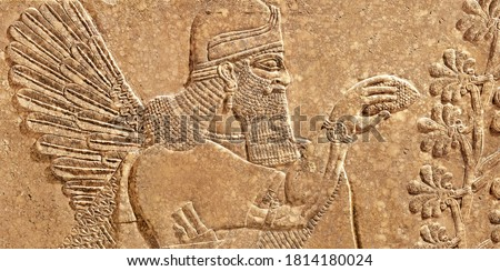 Assyrian wall relief of winged genius, old carving panel from Middle East. Remains of fine art of ancient Babylonian and Sumerian civilization in Mesopotamia. History and mythology of Iran and Iraq.