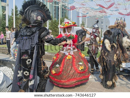 Astana, Kazakhstan - July 6, 2017: Street entertainment, costume hire. Young Kazakh woman in fancy dress of fairy & 3 men rigged out as knight, legionary & shaman #743646127