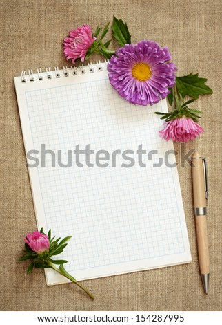 Aster composition on a notepad on gray canvas background