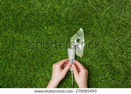 Asthma allergy inhaler sprayer over green grass. Breathing fresh air in nature concept. Horizontal photo.