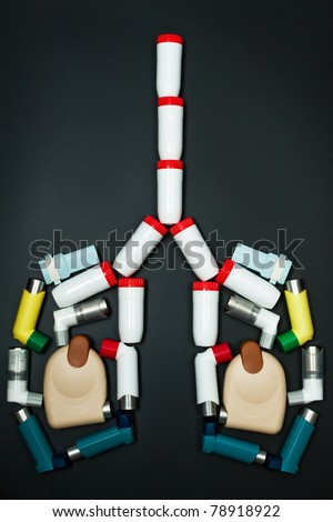 Asthma (chronic bronchitis) inhaler in the form of the human lung on a dark background - stock photo