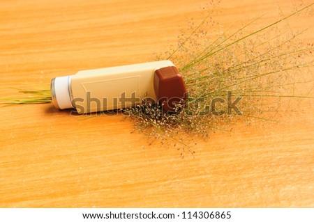 Asthma inhaler and flower of grass