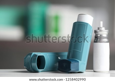 Asthma inhalers on table against blurred background. Space for text Stock photo ©