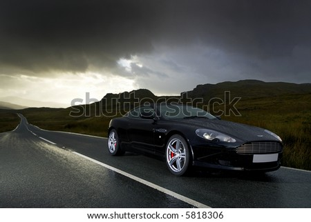 Aston Martin DB9s under a stormy sky - stock photo