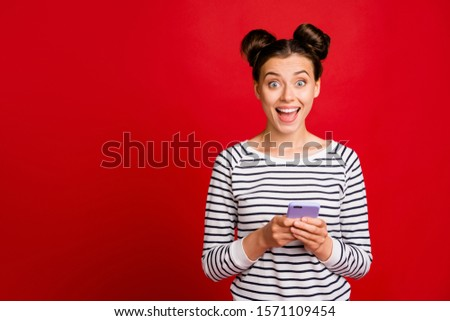 Astonished excited crazy girl use smartphone get blogging social media notification impressed scream wow omg wear casual style white clothes isolated over red color background