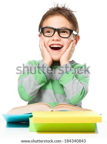 Astonished little boy is reading a book while wearing glasses, isolated over white