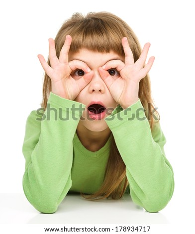 Astonished little girl is showing glasses gesture, isolated over white
