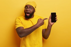 Astonished plump dark skinned man holds mobile phone with copy empty screen, points at device, surprised with high quality gadget and its functions, wears yellow hat and t shirt. Selective focus