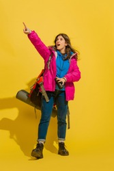 Astonished pointing up. Portrait of a cheerful young caucasian tourist girl with bag and binoculars isolated on yellow studio background. Preparing for traveling. Resort, human emotions, vacation.