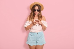 Astonished pretty woman wears blouse with bared shoulders, short, straw hat and sunglasses posing with open mouth, holds her cell phone with surprised facial expression, recives messages from friend.