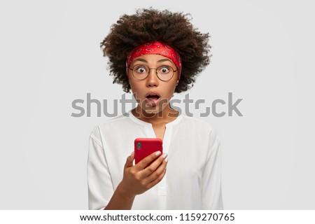 Astonished scared African American woman expresses deep surprisement, holds modern cell phone, recieves bad news, reads something in internet, chatts with friends in social networks, checks email box #1159270765