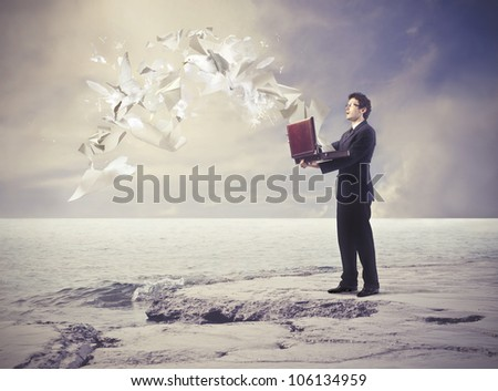 Astonished young businessman with paper sheets flying from his open briefcase