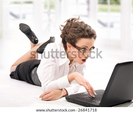 Astonished young businesswoman with laptop on the floor
