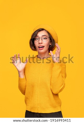 Astonished young female in eyeglasses dressed in yellow knitted sweater and beret looking at camera with amazement and gesturing with raised hands on yellow background Photo stock ©