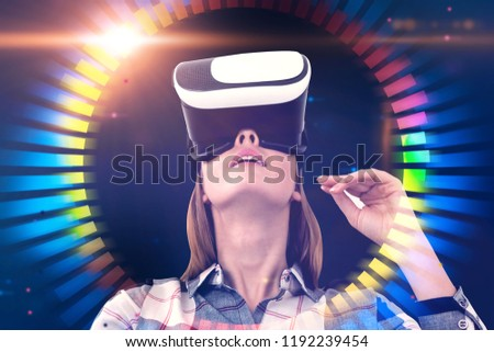 Astonished young woman in checkered shirt and vr glasses looking upwards. Hud and gui interface over dark blue background. Hi tech concept. Toned image double exposure #1192239454