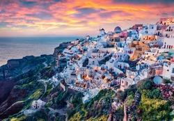 Astonishing evening view of Santorini island. Magnificent summer sunset on famous Greek resort Oia, Greece, Europe. Fantastic seascape of Mediterranena sea. Traveling concept background.