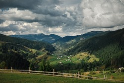 Astonishing panoramic view of Carpathian village and nature on dark moody day with big clouds.
