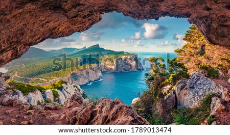 Astonishing summer view of Caccia cape from the small cave in the cliff. Fabulous morning scene of Sardinia island, Italy, Europe. Aerial Mediterranean seascape. Beauty of nature concept background.