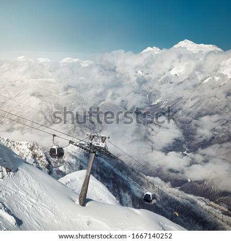 Astonishing view on Caucasus mountains from the Rosa Peak. Snowy mountains and low clouds. Sochi; Krasnaya Polyana (Rosa Khutor alpine ski resort); Western Caucasus; Russia.