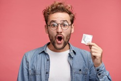Astonsihed male wears spectacles, opens mouth with great surprisment as finds condom in bedroom, doesn`t know who used it. Shocked adult holds rubber condom, isolated over pink studio background