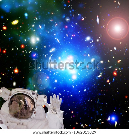 Astroanaut waving. Colorful background. The elements of this image furnished by NASA. #1062013829