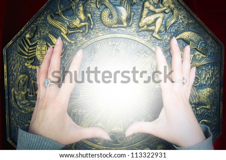 astrologer with hands over zodiac