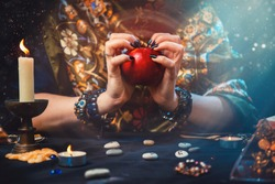 Astrology and divination. A fortune teller holds a red apple in her hands. On the table lay runes, candles, talismans. Close-up of hands