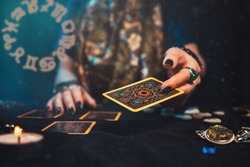 Astrology and divination. A fortune teller holds a tarot card in her hand. The zodiac circle is shown on the left. On the table are runes, candles, talismans. Close-up of hands