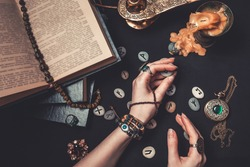 Astrology and esotericism. The witch is guessing on Runestones.Hands close up. On a black background lie fortune-telling runes, a book, precious amulets, a copper lamp and a candle