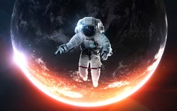 Astronaut at the spacewalk. Awesome beautiful Earth planet in cold and warm light. Elements of this image furnished by NASA