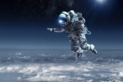 Astronaut floating above clouds