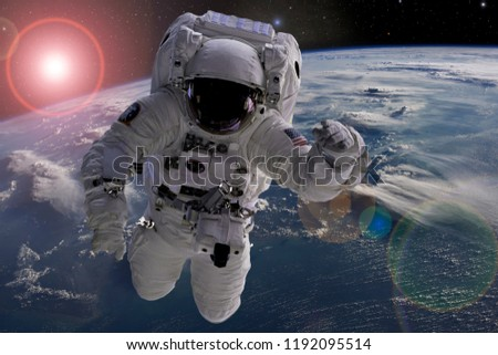 astronaut flying in outer space near planet earth doing some work near space ship