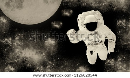 Astronaut in a spacesuit in outer space. Spaceman on the background of the planet. Space landscape. Vintage toned image. Element of this image furnished by NASA