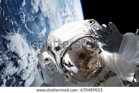 Stock Photo astronaut in orbit of planet Earth waving into the camera (3d illustration, elements of this image are furnished by NASA)