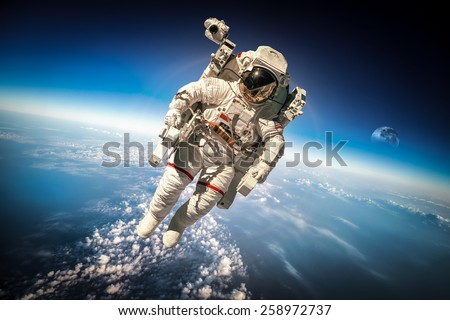Astronaut in outer space against the backdrop of the planet earth. Elements of this image furnished by NASA. #258972737