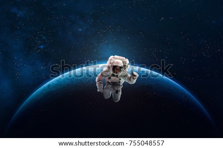 Stock Photo Astronaut in outer space over of the planet Earth. Colorful beautiful planet. Milky way. Blue gradient. Space wallpaper. Elements of this image furnished by NASA