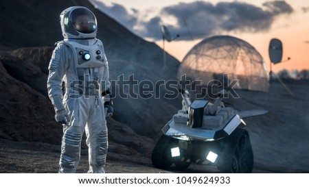 Astronaut in Space Suit Confidently Standing on Alien Planet, Exploration of the the Planet's Surface. In the Background Research Base/ Station and Rover. Space Travel, Colonization Concept. #1049624933
